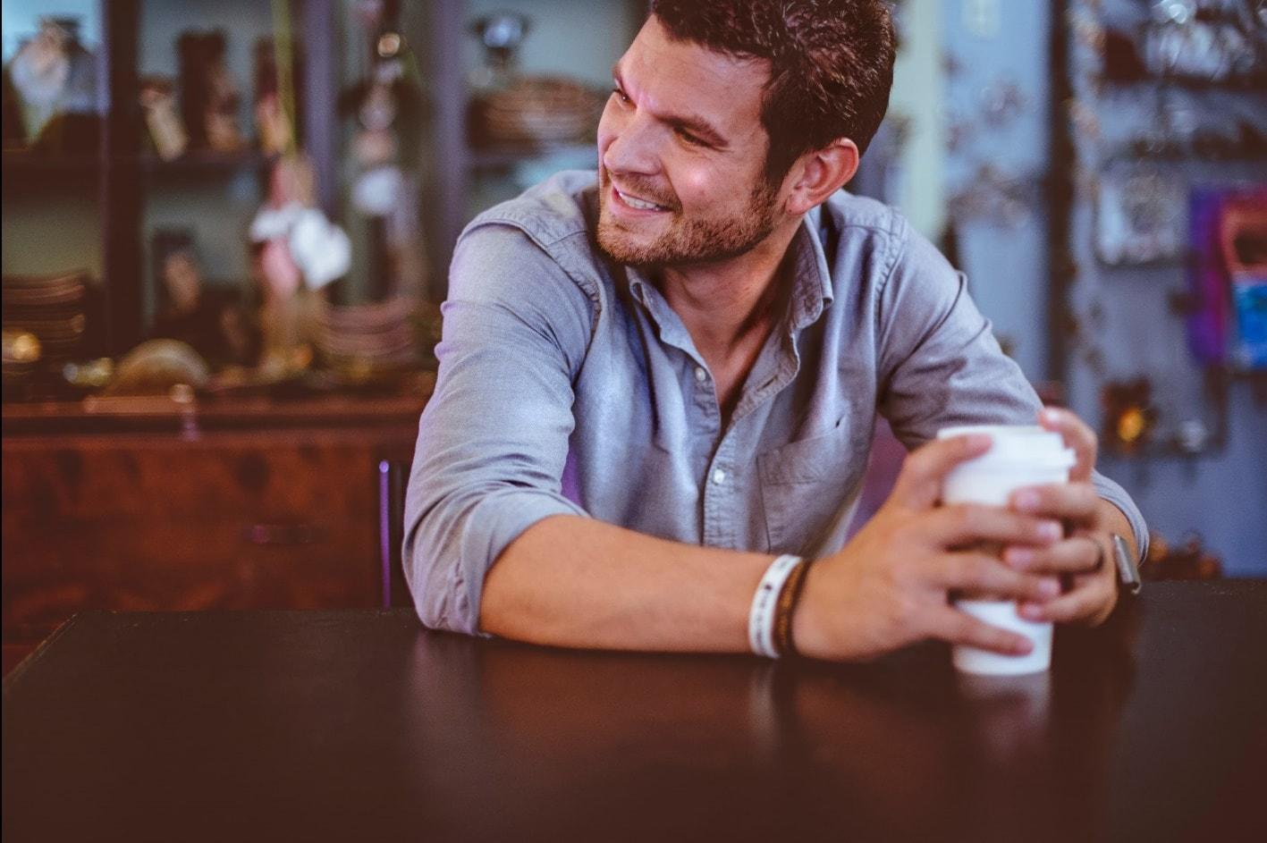 wie werde ich glücklich - lächelnder Mann mit Kaffeebecher
