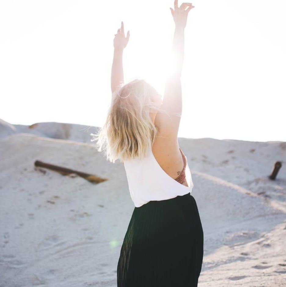 junge Frau die die Hände Richtung Sonne austreckt und glücklich ist